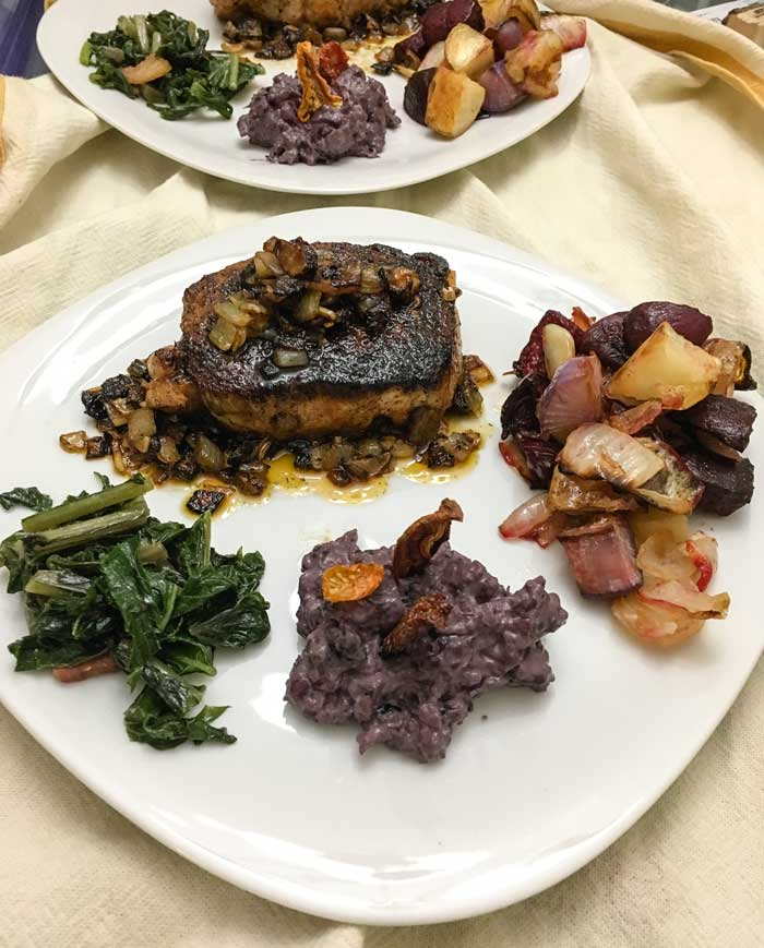 Pork chops with caramelized onions, roasted root veggies, braised rutabaga leaves, and creamed black Incan corn with sun-dried tomatoes.