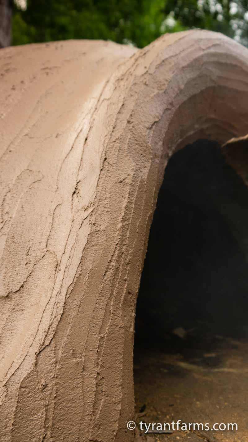 A final look at the wet earthen coating layer around the door of the oven.