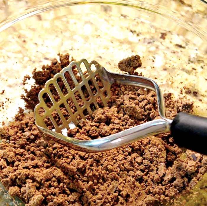mashing leached acorns to make acorn flour
