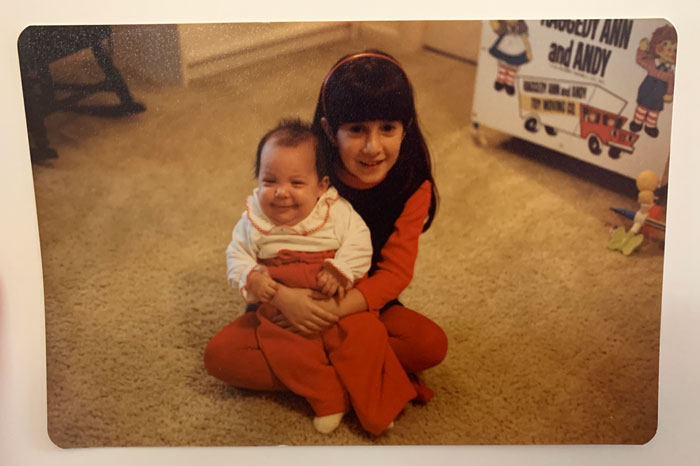 Kids being kids. Baby sister Susan being welcomed into her adopted home by big sis Lisa a few decades ago.