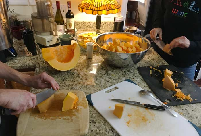 Everybody pitching in on pumpkin chopping. We're getting these prepped into small enough chunks (with skin removed) to fit into a food processor with a grating attachment.