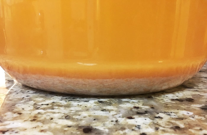 You'll want to rack up the mixture a few more times as it ages and continues fermenting to remove as much lees as possible. Lees is the dead yeast and other precipitate that's heavier than the liquid. If you leave the lees in, you'll end up with a cloudy champagne.