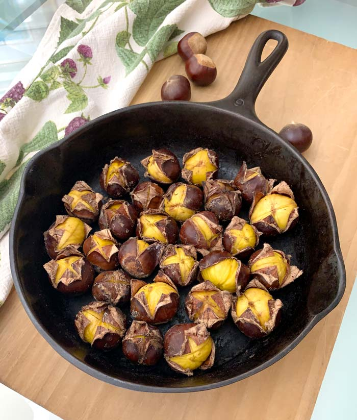 Turn each chestnut cut side up for most visual appeal. We also like to serve them in the same cast iron pan they were cooked in, communal style. Dinner guests can pull each one out as they go. Chestnuts roasted in a cast iron skillet on a stove top.