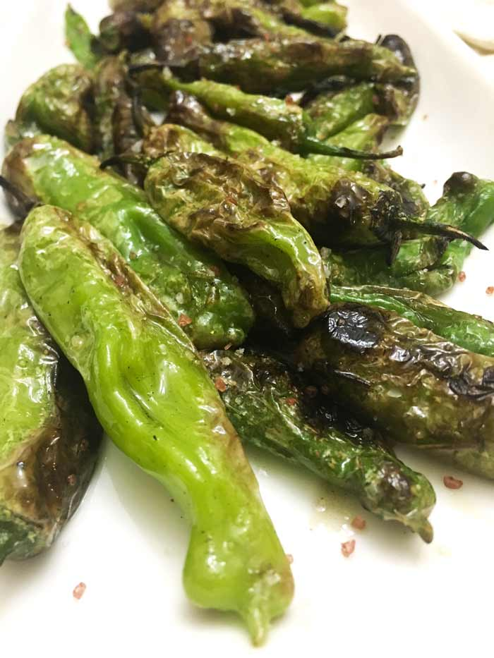 Blistered green Shishito peppers are a perfect summer side.